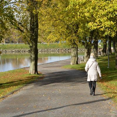 Kvinna går längs en stig nära vattnet i en vacker höstdag.