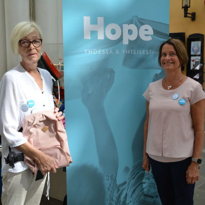 Två kvinnor står leende framför en blå skylt som det står Hope på. Ena kvinnan håller i en rosa ryggsäck.