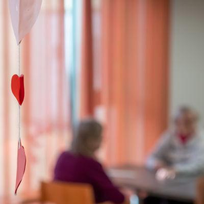 Vanhuksia Myyrmäen vanhustenkeskuksessa kuvattuna epätarkasti läsin läpi.