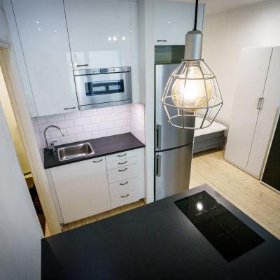 Vaalea yhden huoneen asunto jossa teräksiset mikron ja jääkaapin ovet.