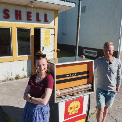 Mies ja nainen nojaavat vanhaa bensiinpumppua vasten. Taustalla pieni puinen kioski, jossa teksti SHELL.