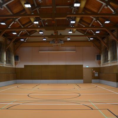 En vy över gymnastiksalen. Längst ner golvet i orangebrunt.