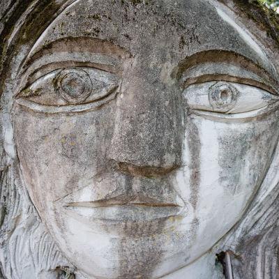Lähikuva harmaasta patsaasta, jossa kasvot ja suuret silmät, taustalla koivikkoa