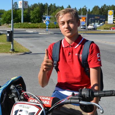 En 16-årig pojke sitter på en moped och visar tummen upp.