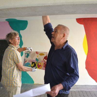 Konstnärerna arbetar i tunneln, Ylva håller en skiss över hur väggen ska se ut: grönt, rött, gult ska det bli.