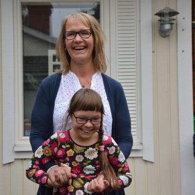 Maria Backman står med dottern Lotta framför sig utanför deras hus. Båda ler.