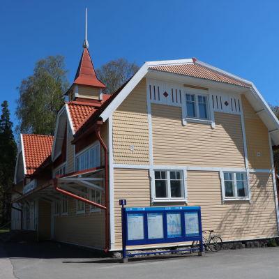 Grankulla tågstation en solig dag. Stationen är ett gult trähus.