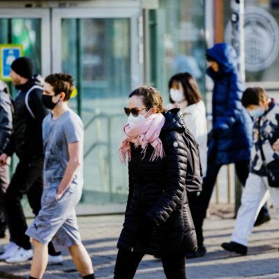 Ihmisiä hengityssuojaimet kasvoilla Helsingin keskustassa.