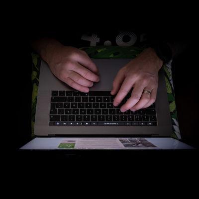 Miehen kädet kirjoittaa kannettavalla tietokoneella.