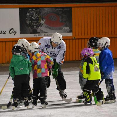 En ledare visar hur man ska hålla i klubban, barn står runt i ring och gör efter.