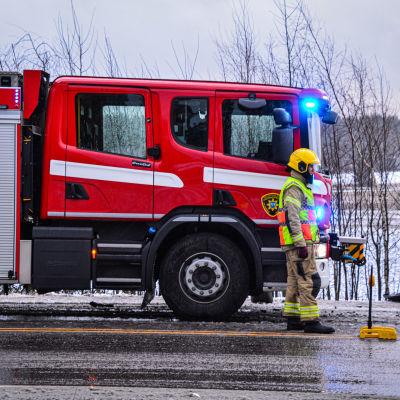 Brandman står vid brandbil på slaskig väg