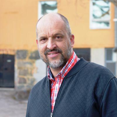 Ett porträtt på en man iklädd skjorta och tröja. Mannen heter Sture Lindholm