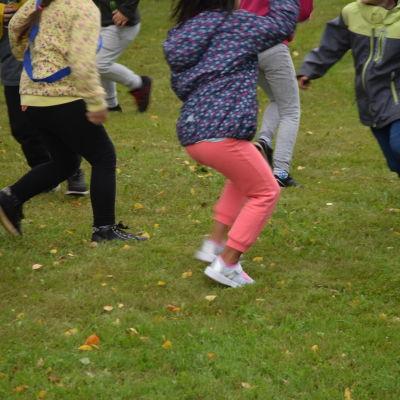 barnfötter och ben som springer runt på gräsmatta. Man ser inte huvuden på barnen.