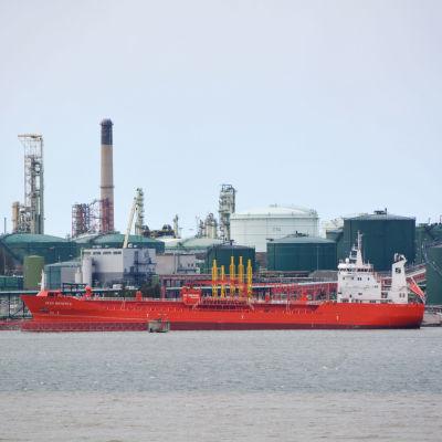 Ett rött lastfartyg vid hamnen i Sköldvik.