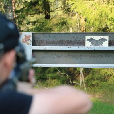 En pojke skjuter med ett luftgevär mot en tavla.
