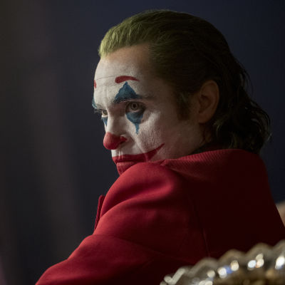 Närbild på Joker (Joaquin Phoenix) iklädd clownmask och röd kostym.