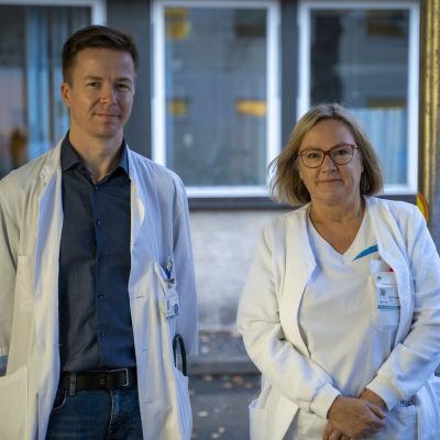 En man i läkarrock och en kvinnlig sjukskötare står och tittar in i kameran.