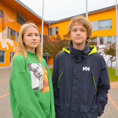 En flicka och en pojke framför en skolbyggnad.