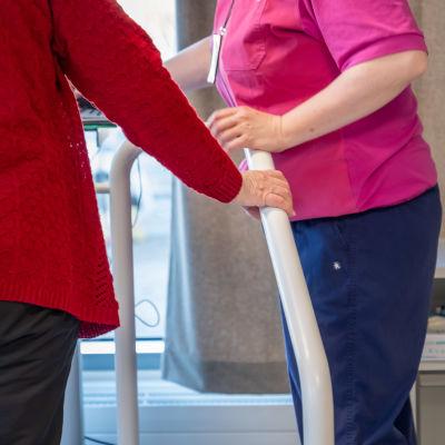 Lähikuva vanhuksesta joka pelaa tasapainopelia fysioterapeutin avustuksella.