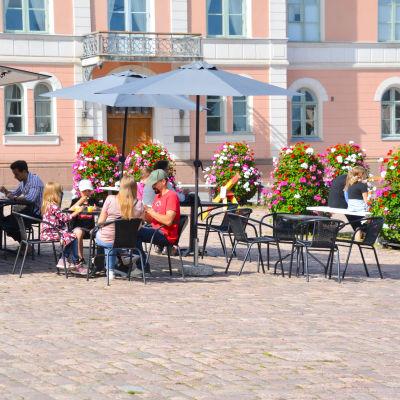 Folk som sitter på ett torgcafé.