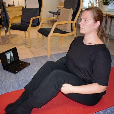 Syöpää sairastava Sonja Alanko jumppaa läppärin edessä.