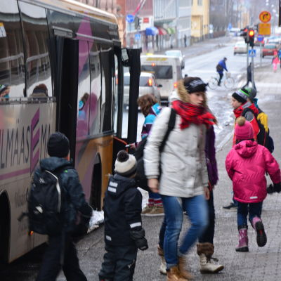 Folk stiger av bussen.