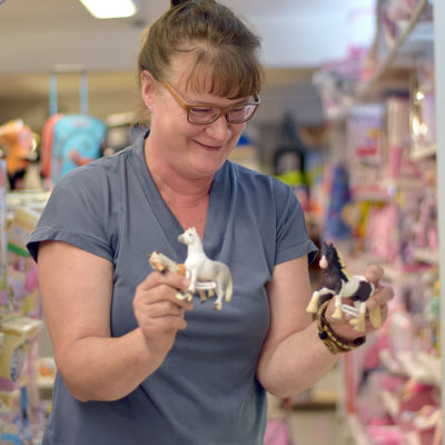 Ella Damén håller upp tre olika hästraser av butikens djurfigurer..
