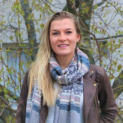 Corinne Grönholm står framför ett träd.