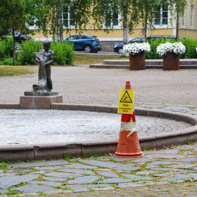 Vattenfontänen i stadsparken i Borgå utan vatten i sig. Bredvid fontänens bassäng står en skylt som varnar för halt botten.