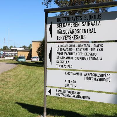 En skylt på en gräsmatta i Kristinestad. Skylten visar riktningen mot hälsovårdscentralen.