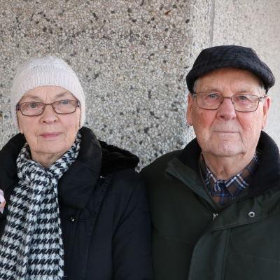 En äldre dam med vit mössa och svartvit randig halsduk står bredvid en äldre herreman med glasögon och svart huvudbonad.