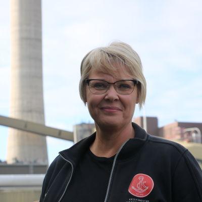 En kvinna med kort ljust hår och glasögon står framför ett kraftverk.