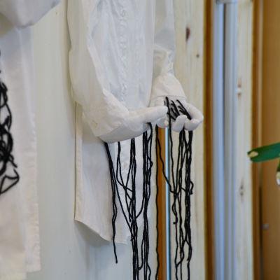 En vit kragskjorta hänger på en vägg. Vid ärmarna finns två händer gjorda av textil som det hänger svarta trådar ifrån.
