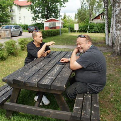 två män sitter vid ett terassbord