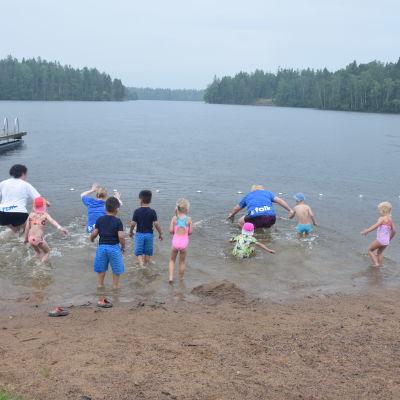 Ett tiotal barn och några vuxna kvinnor springer ut i vattnet vid en strand.