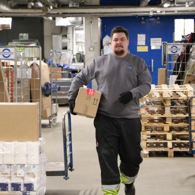 Mathias Rosenlund går i en logistikcentral iklädd arbetskläder med ett paket under armen.