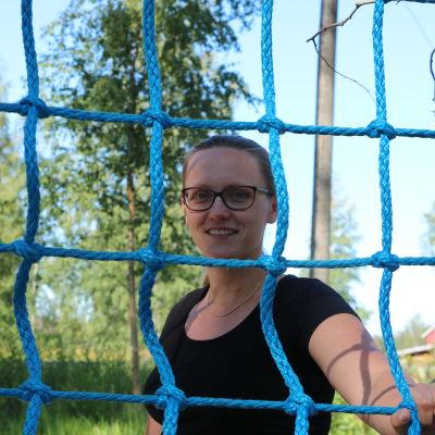 En kvinna med glasögon står bakom en klätterställning gjord av rep.