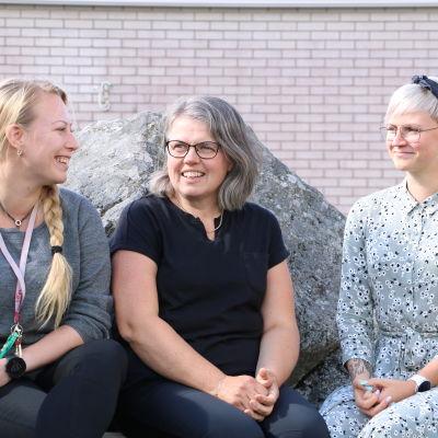 Tre kvinnor sitter intill en stor sten.