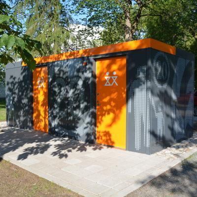 ny offentlig toalett i kuppisparken i åbo. grå rektangylär byggnad med orangea dörrar som stark kontrast.
