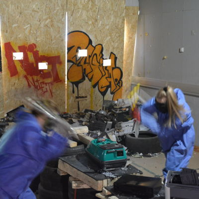 Tre människor står och slår sönder saker med yxor och metallstänger.