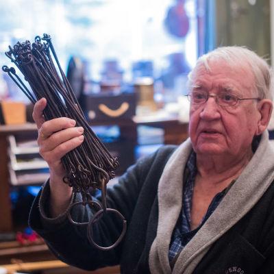 En man håller i en gammal lantmäterirked.