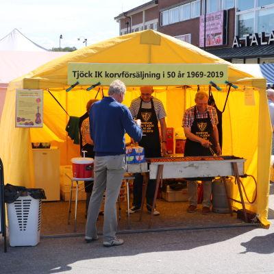 Tre personer står inne i ett gult tält och säljer korv.