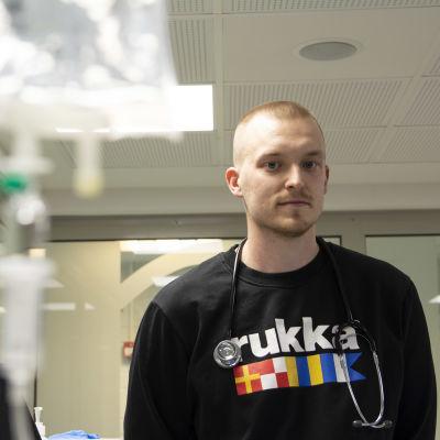 Sairaanhoitajaopiskelija Mikko Huovisen kaulassa roikkuu stetoskooppi, ja hän katsoo suoraan kameraan.
