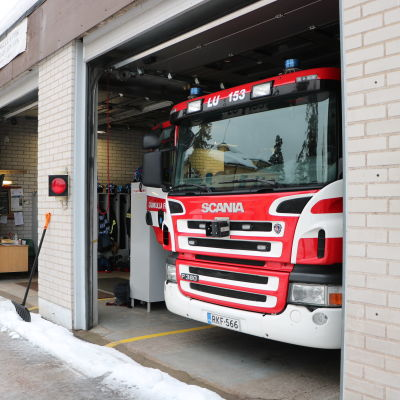 En brandstation med en av garageportarna öppna med en brandbil parkerad i hallen.
