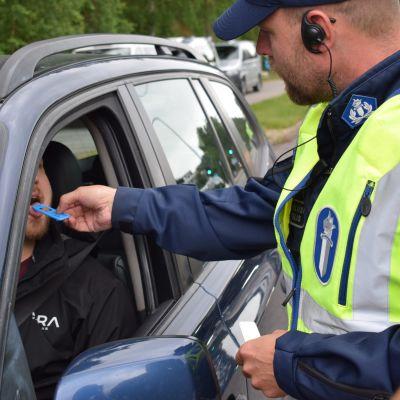 Polis utför ett blårstest för bilist som sitter i sin blåa bil.