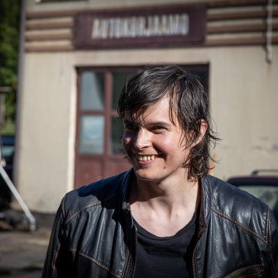 Johannes Holopainen hymyilee rakennuksen edessä nahkatakissaan. Takana autokorjaamo ja kuvauskalustoa.