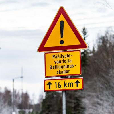 Päällystevaurioista varoittava liikennemerkki maantiellä.