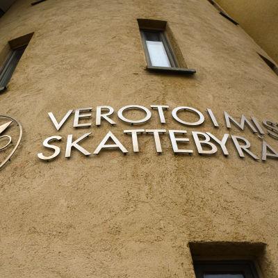 Skattebyråns logo på en rappad gul vägg.