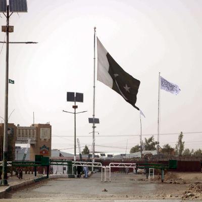Den här bilden på gränsövergången Spin Boldak är tagen från den pakistanska sidan om gränsen. I bakgrunden, på den afghanska sidan, syns talibanernas vita flagga. Flaggan pryds av den muslimska trosbekännelsen.