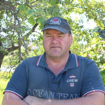 En man med keps på huvudet och blå pikéskjorta står under ett äppelträd.